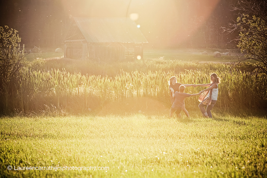 Beautiful family portrait with nature, sun flare and children playing